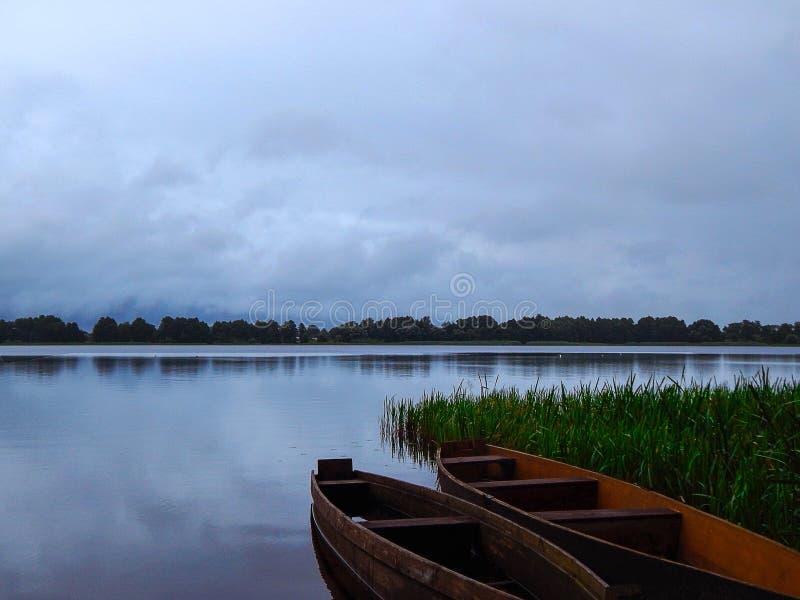 Łódź na jeziorze między zieloną trawą obraz royalty free