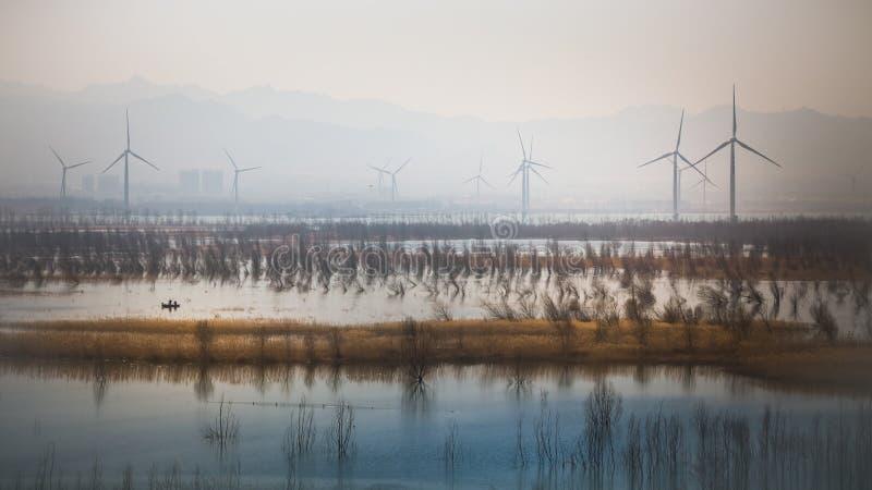 Łódź na jeziorze z wiatraczkiem w tle obraz stock