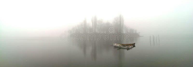 Łódź na mglistym jeziorze obraz stock