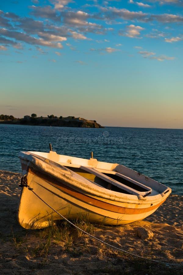 Łódź na plaży przy zmierzchem z ruinami stary rzymski forteca w backround, Sithonia obrazy stock