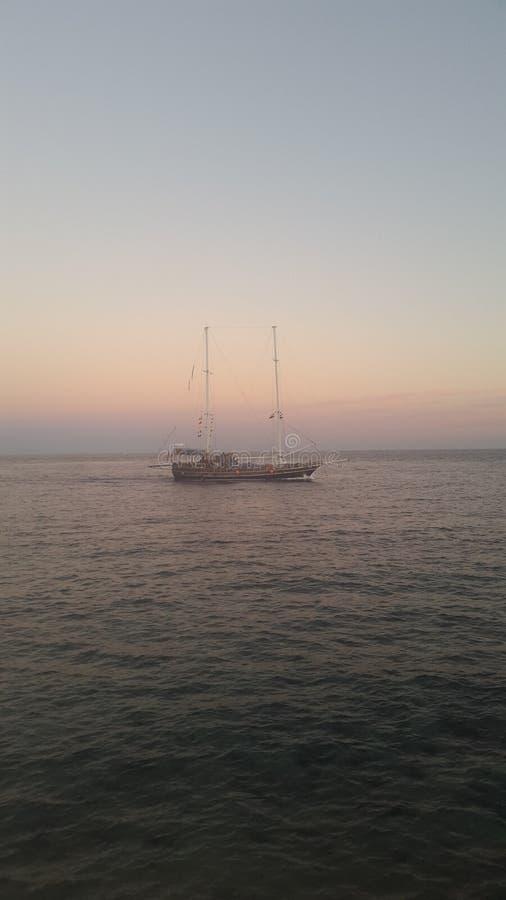 Łódź przy zmierzchem w czerwonym morzu obraz royalty free