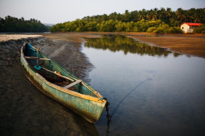 Łódź rybacka na brzeg rzeki w zwrotnikach z drzewkami palmowymi w wieczór, obraz stock