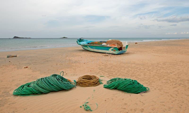 Łódź rybacka obok arkan i sieci na Nilaveli Wyrzucać na brzeg w Trincomalee stanie w Sri Lanka zdjęcia royalty free