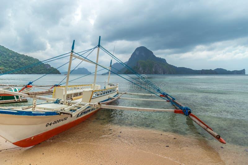Łódź rybacka splatał i cumował przy plażą w dżdżystym ranku w El Nido, Palawan, Filipiny zdjęcie stock