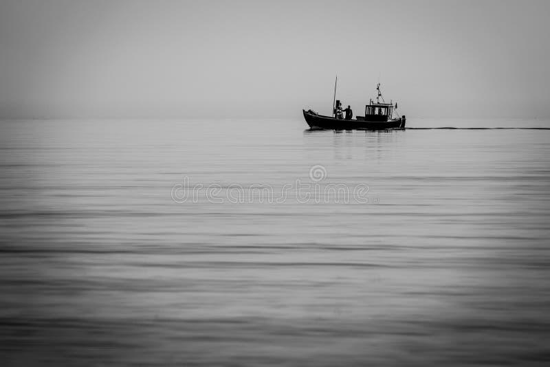 Łódź rybacka wychodzi morze wcześnie rano gdy morze jest spokojny zdjęcie royalty free