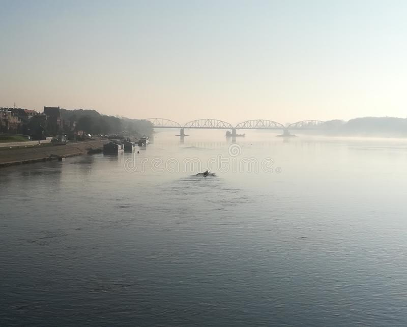 Łódź usuwa most w mgle na rzece obraz stock