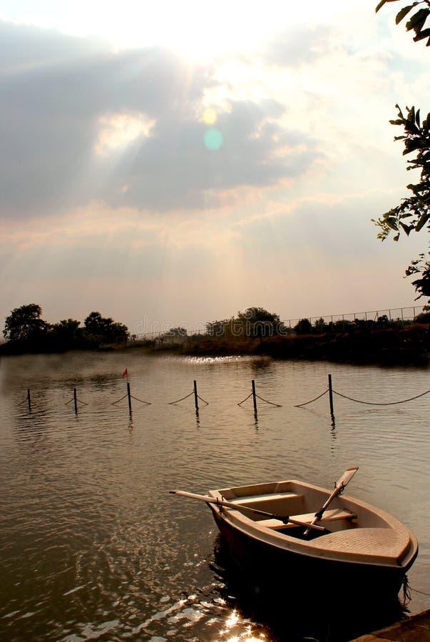 Łódź w jeziorze z zmierzchu niebem przy sittanavasal jamy świątyni kompleksem obraz stock