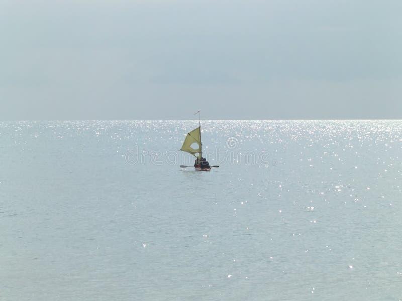 Łódź z żaglem i wiosłami unosi się morzem fotografia royalty free