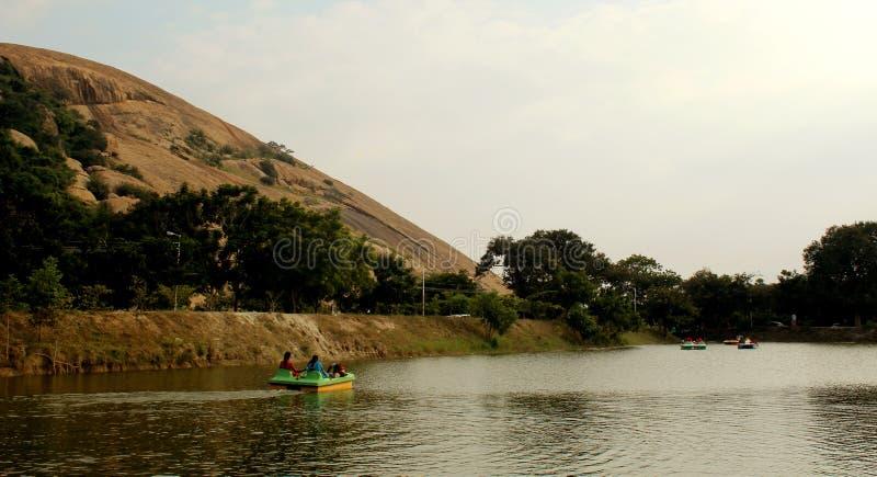 Łódkowaci jeźdzowie w jeziorze z wzgórzami przy sittanavasal jamy świątyni kompleksem obraz royalty free