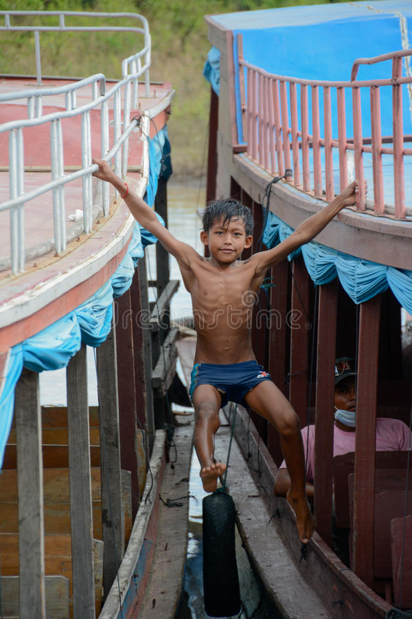 Łódkowata Kołysząca chłopiec przy Tonle aproszy Jeziorną wioską rybacką Kambodża zdjęcie royalty free