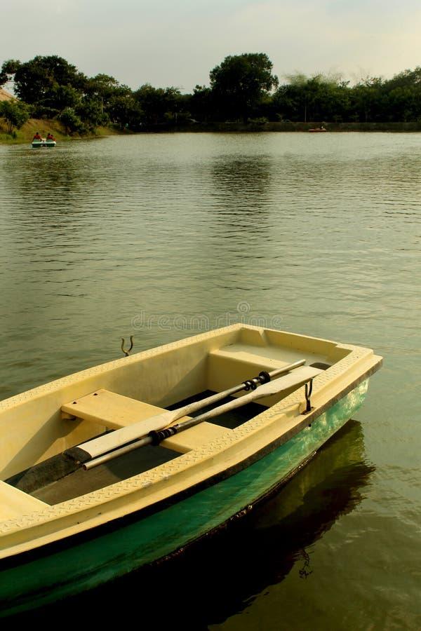 Łódkowaty czekanie dla jeźdzów z paddles w jeziorze przy sittanavasal jamy świątyni kompleksem obraz stock