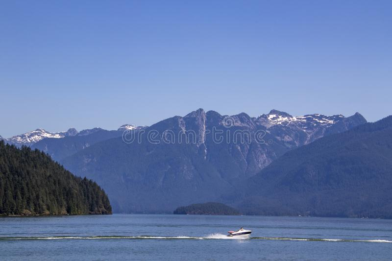 Łódkowaty jeżdżenie na wodzie z górami w tle obrazy stock