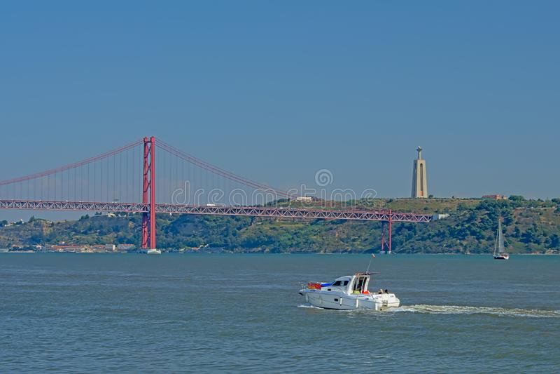 Łódkowaty kłoszenie Ponte 25 De Abril most z Christo Reja statuą na bulwarze w Lisbon, fotografia royalty free