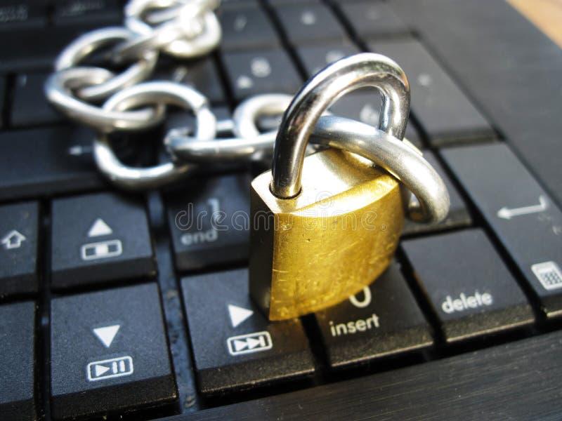 Łańcuch i kędziorek na laptop klawiaturze Komputerowy zakaz, interneta zakaz uzależnienie Anty wirus zdjęcie stock