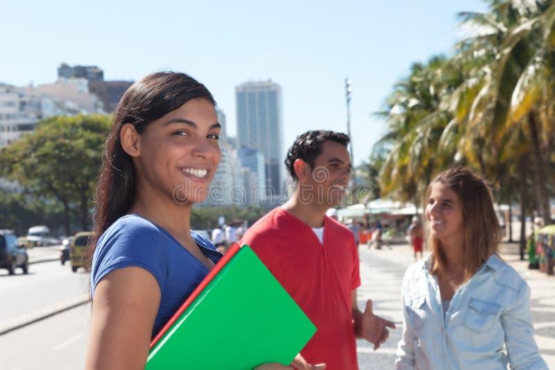 Łaciński żeński uczeń z przyjaciółmi w mieście fotografia stock