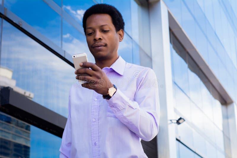 Łaciński biznesmen używa telefon komórkowego w mieście obrazy stock