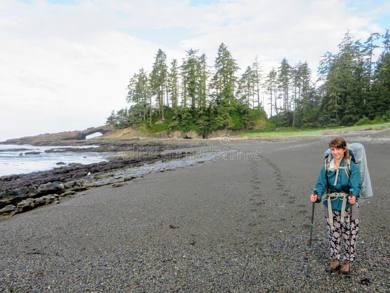 Ładna żeńska wycieczkowicz pozycja na plaży zachodnie wybrzeże ślad na Vancouver wyspie, kolumbia brytyjska, Kanada zdjęcie royalty free