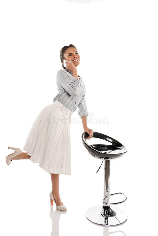 Ładna amerykanin afrykańskiego pochodzenia szpilki dziewczyna opowiada na smartphone podczas gdy opierający na krześle zdjęcia stock