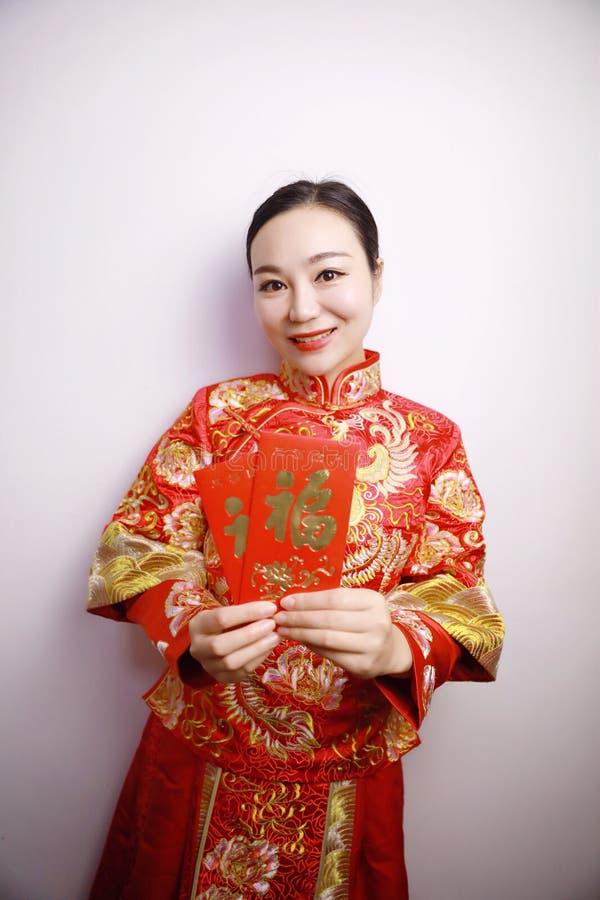 Ładna Azjatycka Chińska piękna uśmiech panna młoda z tradycyjni chińskie czerwieni sukni ślubną ręką z czerwoną papierową torbą n obraz stock
