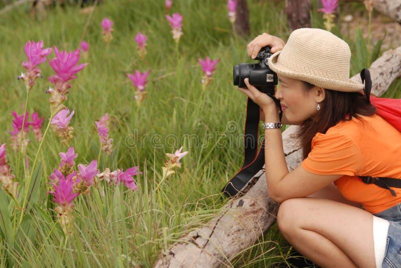 Ładna Azjatycka kobieta bierze fotografię na kwiatu polu. obrazy stock