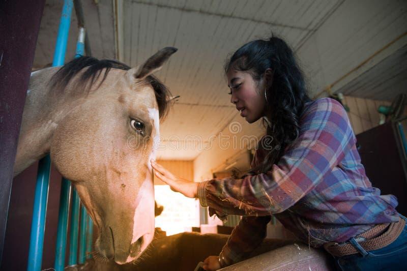 Ładna Azjatycka kobieta migdali konia w gospodarstwie rolnym zdjęcia royalty free