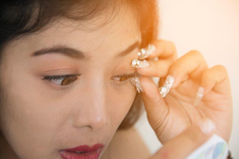 Ładna Azjatycka kobieta wtyka sztuczne rzęsy ona zdjęcia royalty free