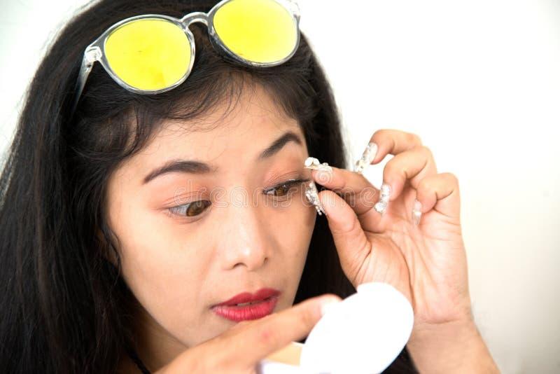 Ładna Azjatycka kobieta wtyka sztuczne rzęsy ona fotografia stock