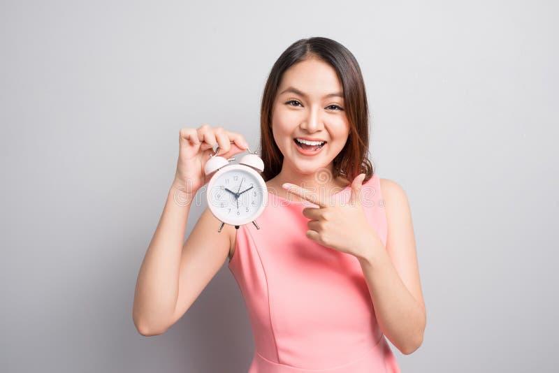 Ładna azjatykcia dziewczyna trzyma budzika wewnątrz z zdziwioną twarzą zdjęcia royalty free