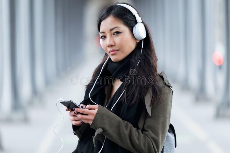 Ładna azjatykcia młoda kobieta słucha muzyczna i patrzeje kamera w ulicie fotografia stock