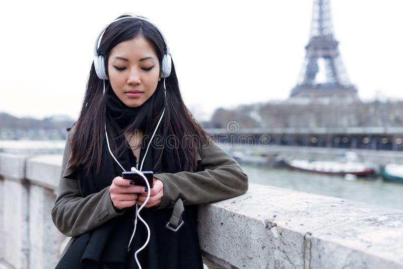 Ładna azjatykcia młoda kobieta słucha muzyka z telefonem komórkowym przed wieżą eifla w Paryż obrazy stock