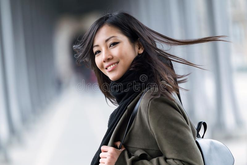 Ładna azjatykcia młoda kobieta uśmiechnięta i patrzeje kamerę w ulicie fotografia royalty free