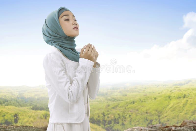 Ładna azjatykcia muzułmańska kobieta jest ubranym hijab dźwigania modlenie i rękę zdjęcia stock