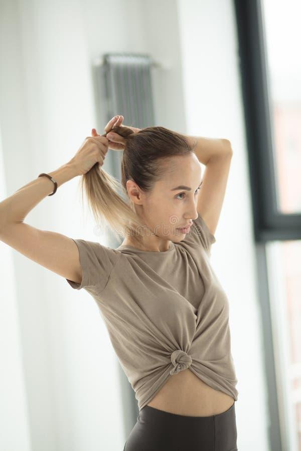 Ładna blond kobieta trenująca sprząta jej włosy podczas gdy obraz stock