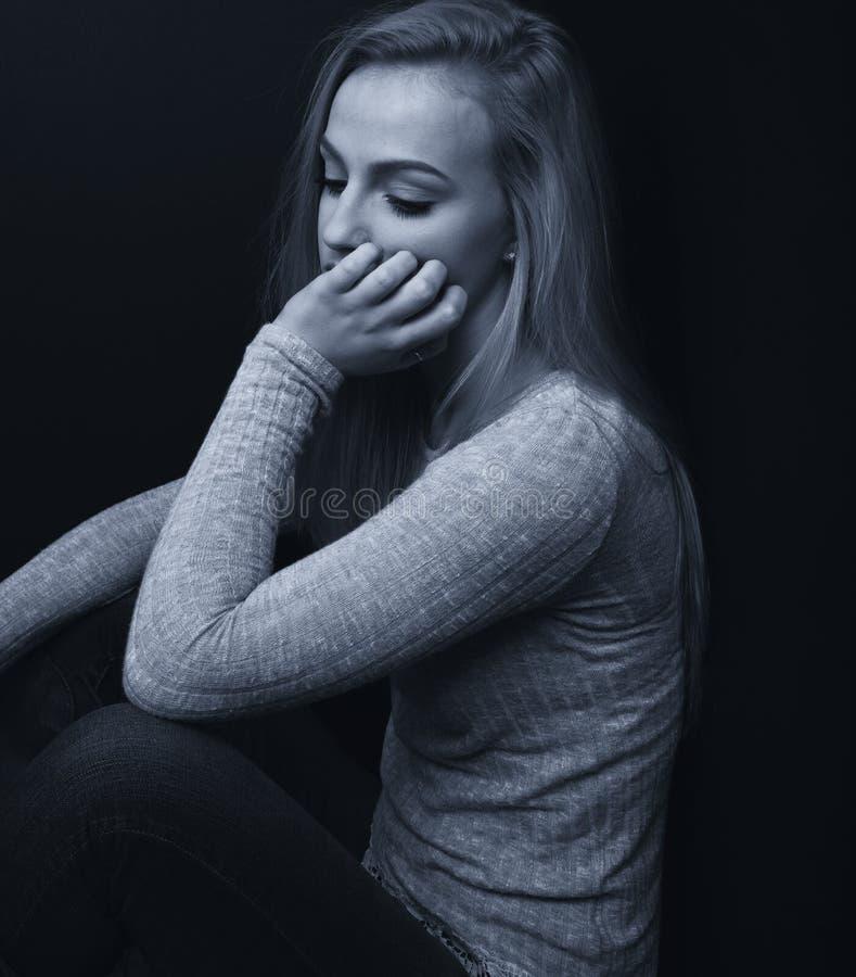 Ładna blond nastoletnia dziewczyna patrzeje smutny z jeden ręką na jej twarzy zdjęcie stock