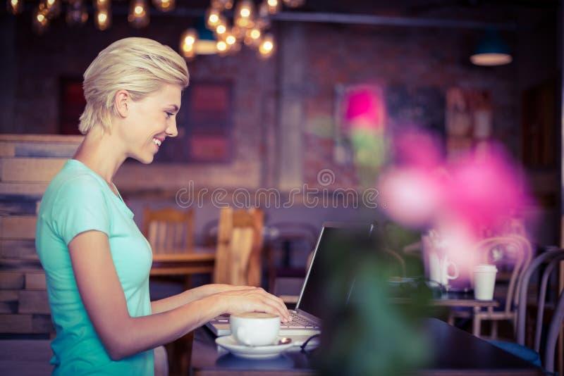 Ładna blondynka używa laptop fotografia stock