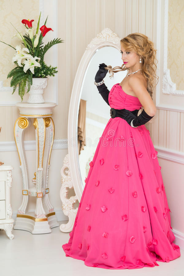 Ładna blondynka w długiej czerwieni sukni stoi obok lustra zdjęcie stock