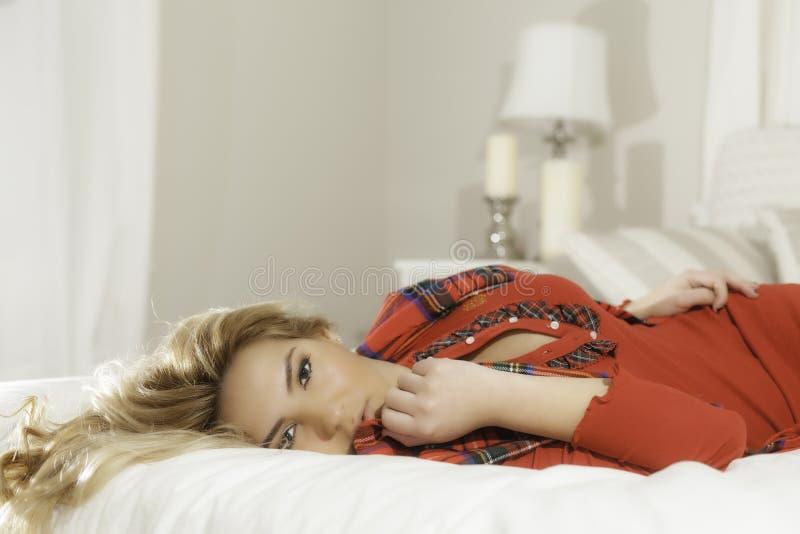Ładna blondynki dziewczyna Kłaść na Łóżkowym Lampowym tle W rewolucjonistce fotografia stock