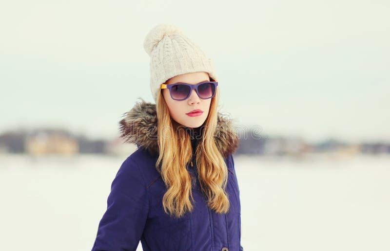 Ładna blondynki kobieta jest ubranym kurtkę, kapelusz i okulary przeciwsłonecznych, obraz royalty free