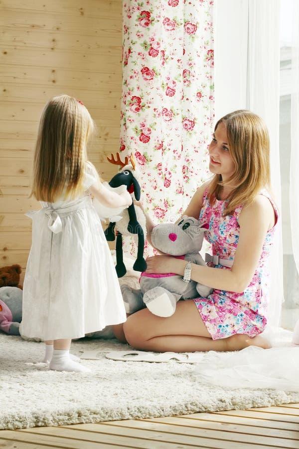 Ładna blondynki mała dziewczynka i jej macierzysta sztuka z miękkimi zabawkami zdjęcia royalty free
