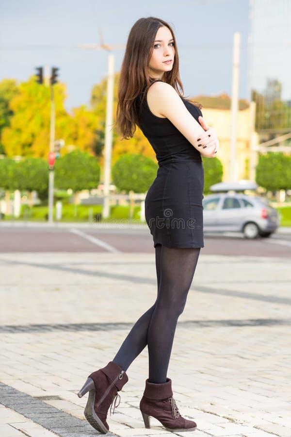 Ładna brunetka jest ubranym czerni suknię obrazy royalty free