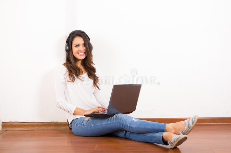Ładna brunetka jest ubranym drelichowych cajgi i bielu wierzchołek obrazy stock