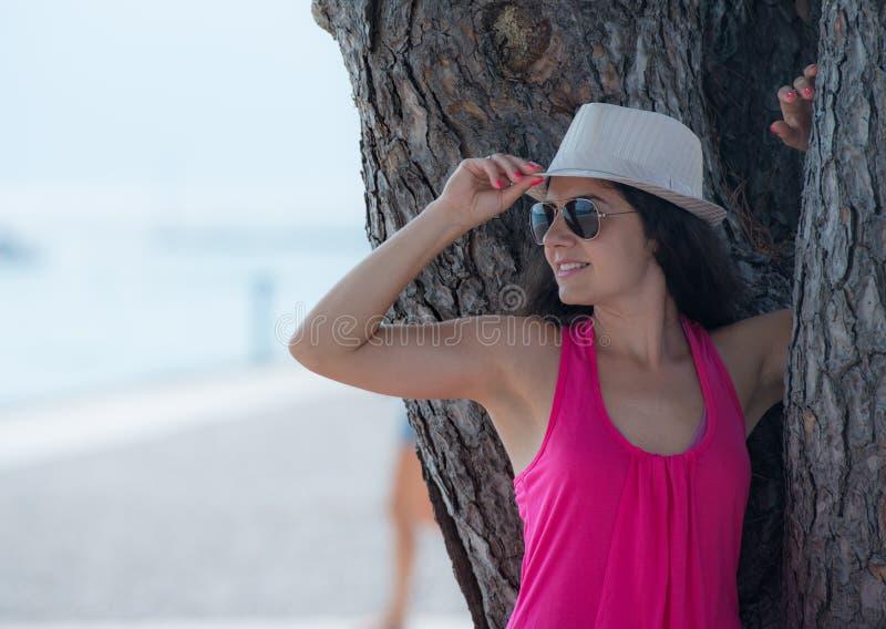 Ładna brunetka pozuje blisko drzewa obrazy stock