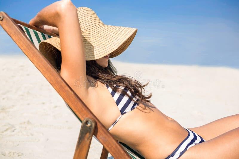 Ładna brunetka relaksuje na pokładu krześle przy plażą zdjęcia stock