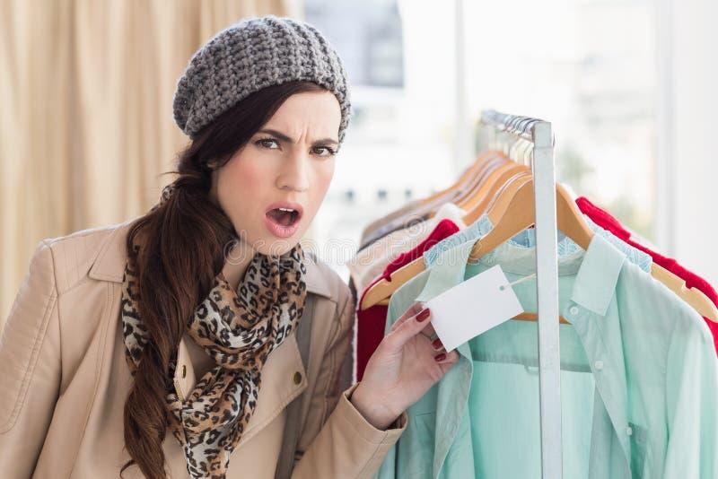 Ładna brunetka szokująca przy ceną koszula zdjęcie stock