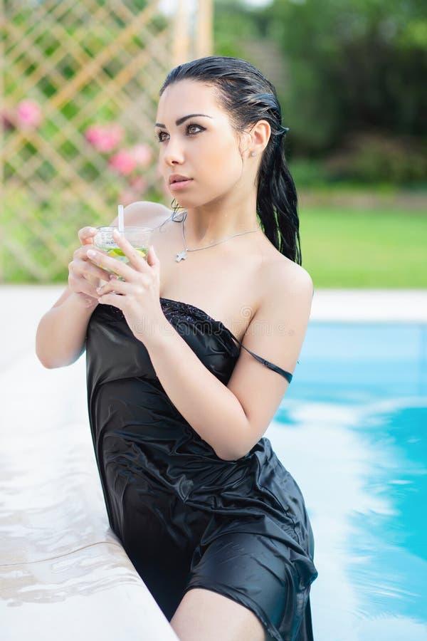 Ładna brunetka ubierająca w czarnej sukni zdjęcia stock