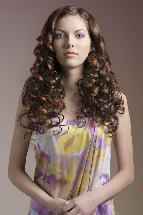 Ładna brunetka z kędzierzawym włosy przed kamerą fotografia stock