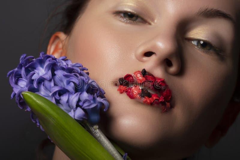 Ładna brunetki kobieta z czerwony kreatywnie uzupełnia blisko jej twarzy i błękitny hiacyntowy kwiat Zamyka w górę piękna pojęcia fotografia stock