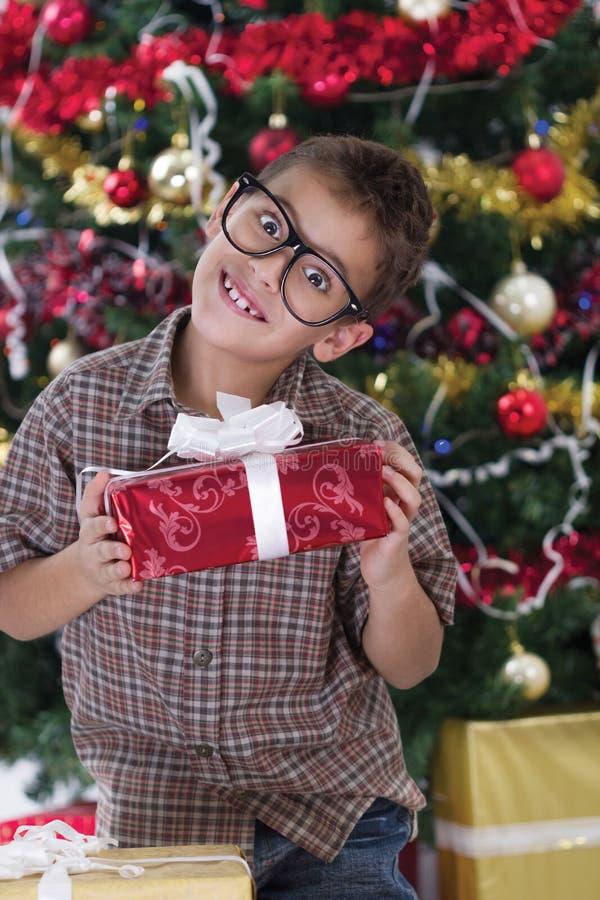 Ładna chłopiec ono uśmiecha się z teraźniejszością blisko choinki obrazy royalty free