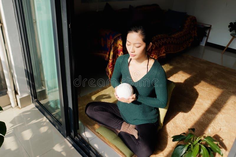 Ładna Chińska młoda kobieta medytuje w domu, siedzący na podłogowej mienie księżyc piłce w słońca świetle obraz stock