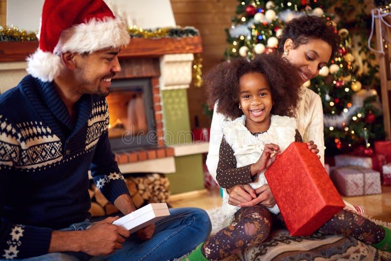 Ładna czarna dziewczyna z rodzicami otwiera Bożenarodzeniowych prezenty obrazy royalty free